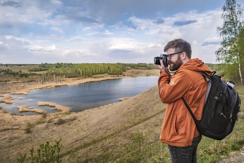En skäggig man - en turist med en ryggsäck står överst av en kulle, rymmer en kamera i hans händer och tar bilder av ett härligt royaltyfri fotografi