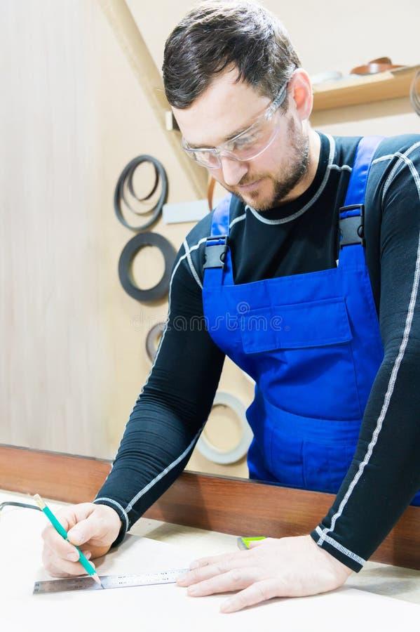 En skäggig trött stilig snickare på en tabell med en blyertspenna drar ett tecken på brädet På arbetsplatsen finns det arkivfoton