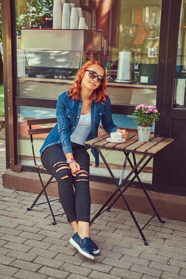 En skönhetrödhårig manflicka dricker kaffe som sitter nära coffee shop royaltyfria bilder
