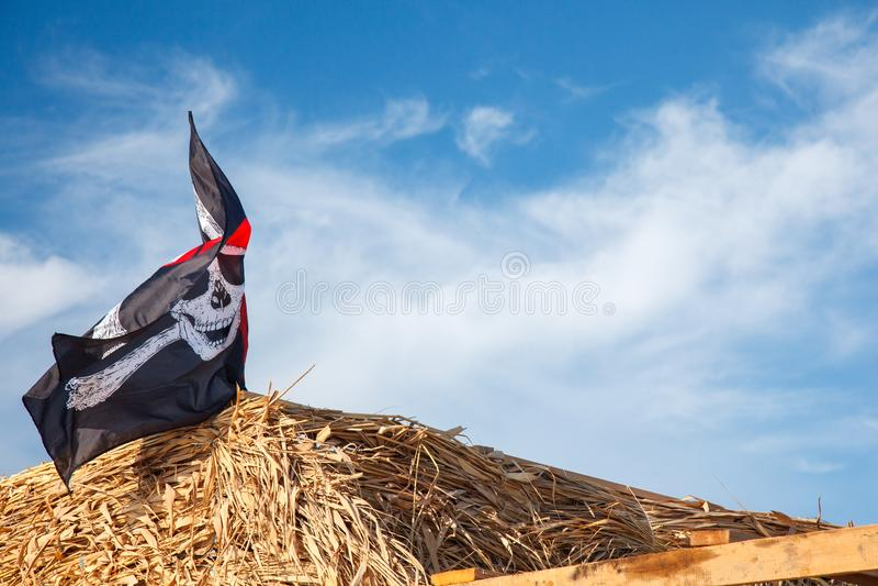 En skalle och korslagda benknotor piratkopierar flaggan som vinkar i vinden , Piratkopierar Jolly Roger, flaggan arkivfoto