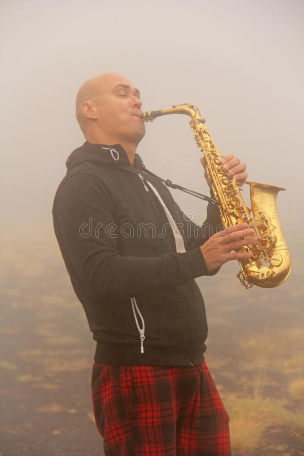 En skallig man spelar på en guld- alt- saxofon i naturen, mot fotografering för bildbyråer
