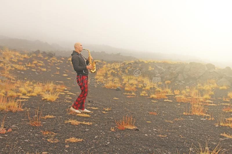 En skallig man spelar på en guld- alt- saxofon i naturen, mot royaltyfria bilder