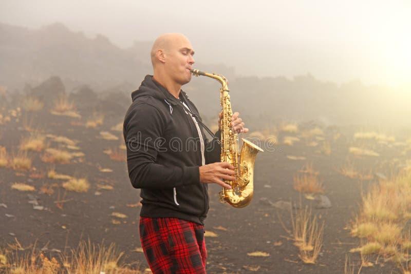 En skallig man spelar på en guld- alt- saxofon i naturen, mot arkivfoto