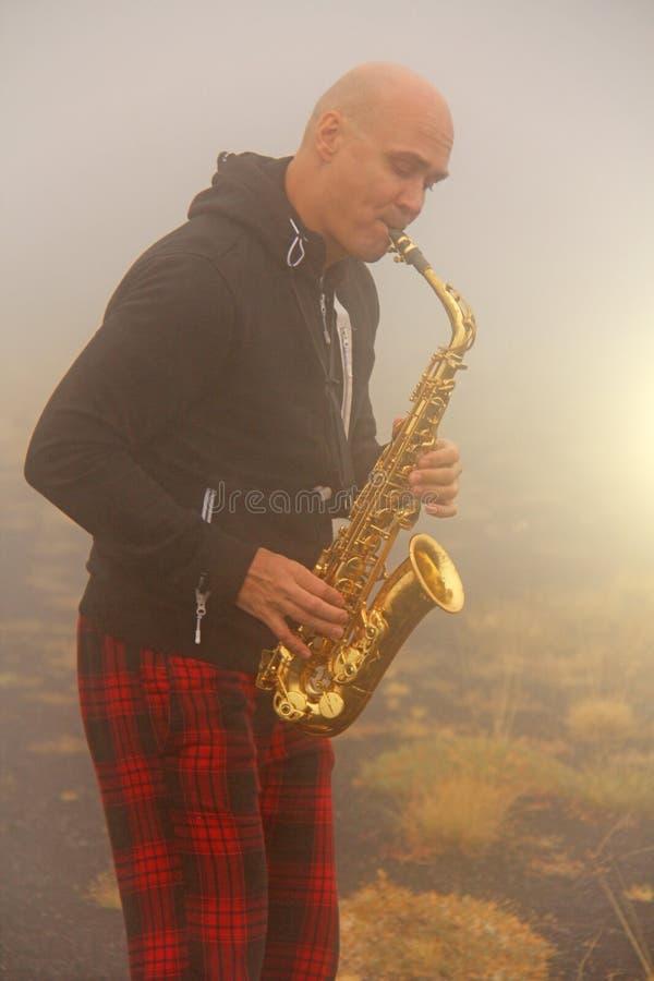 En skallig man spelar på en guld- alt- saxofon i naturen, mot arkivbilder