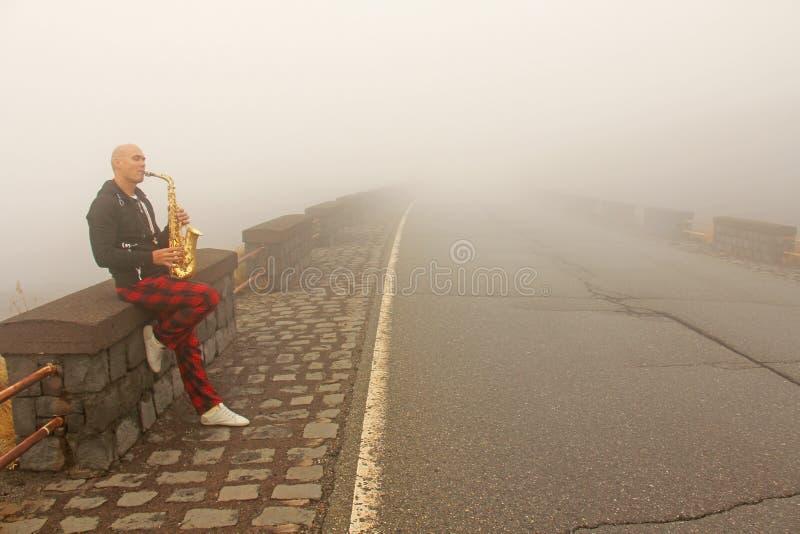 En skallig man spelar på en guld- alt- saxofon på vägrenen, igen royaltyfri foto