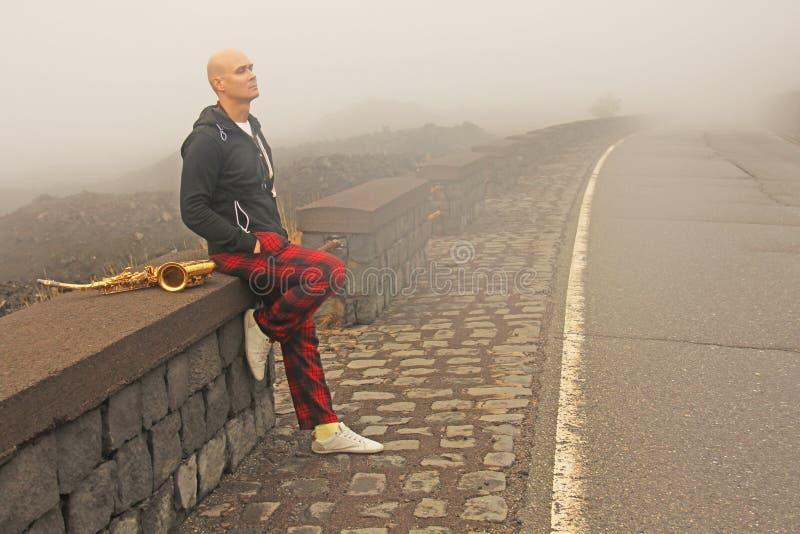 En skallig man spelar på en guld- alt- saxofon på vägrenen, igen fotografering för bildbyråer