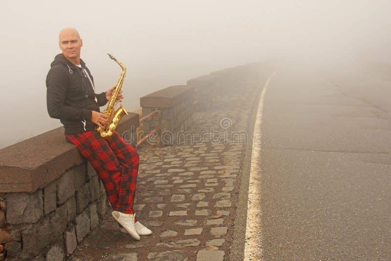 En skallig man spelar på en guld- alt- saxofon på vägrenen, igen arkivfoto