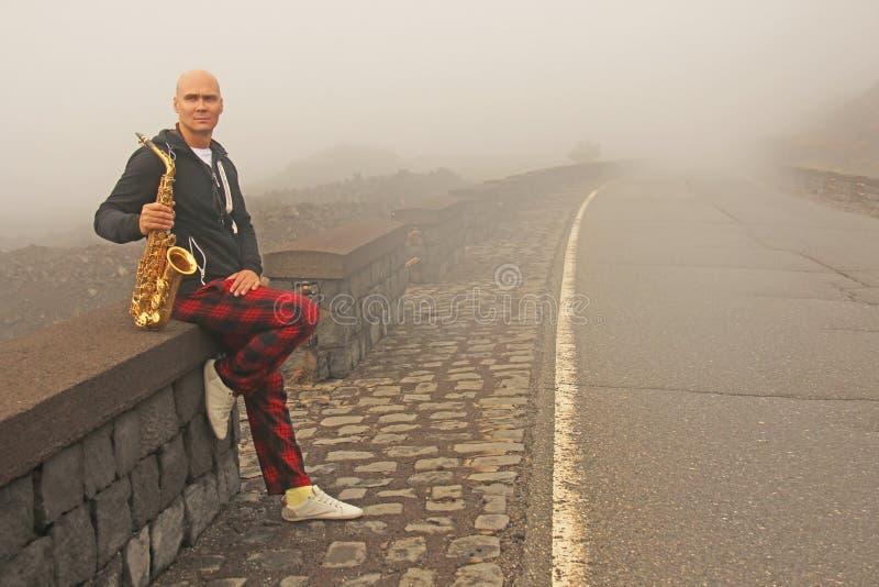 En skallig man spelar på en guld- alt- saxofon på vägrenen, igen arkivbild