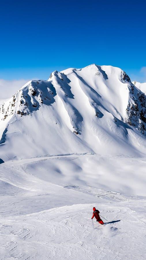 En skidåkare bara på skida sluttar med toppmötena och blåtten sk