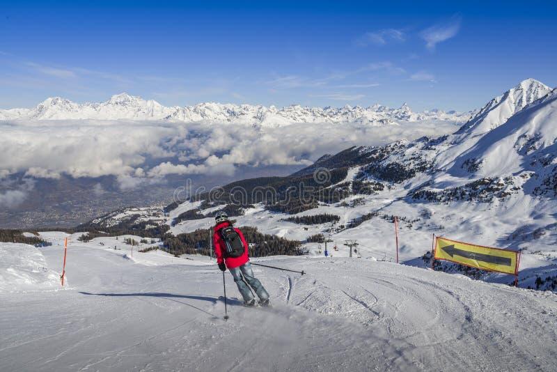 En skidåkare i jeans som går sluttande en piste med den ansade panoramautsikten av brett och, skidar pisten Sikten in mot nord är royaltyfri foto