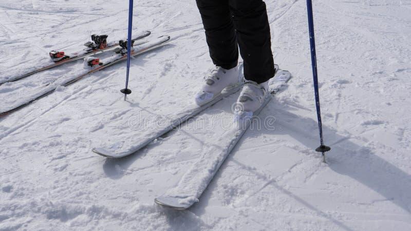 En skidåkare sätter på hans sluttande Ski On White Ski Boots royaltyfria foton