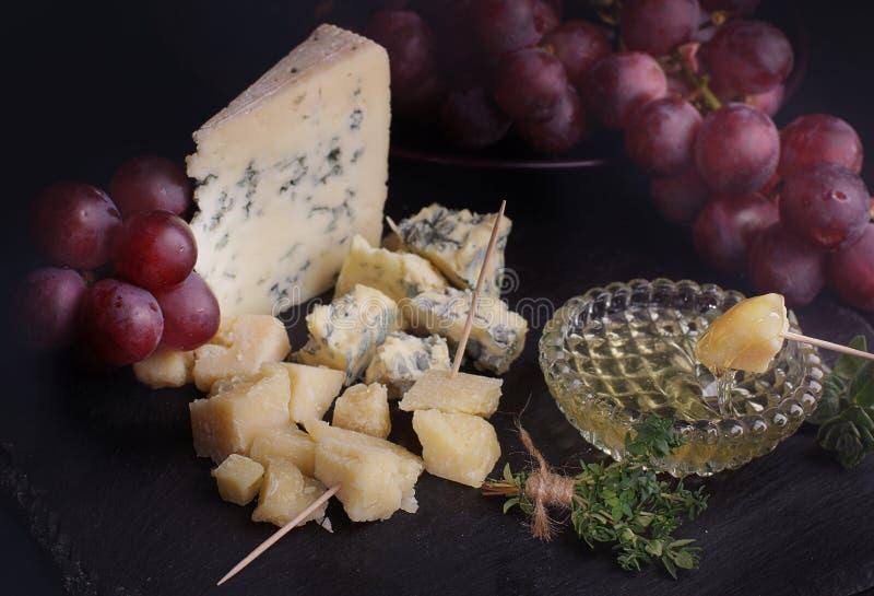 En skiva av ost i honung, innan att äta med druvor Nära kryddiga örter arkivfoton