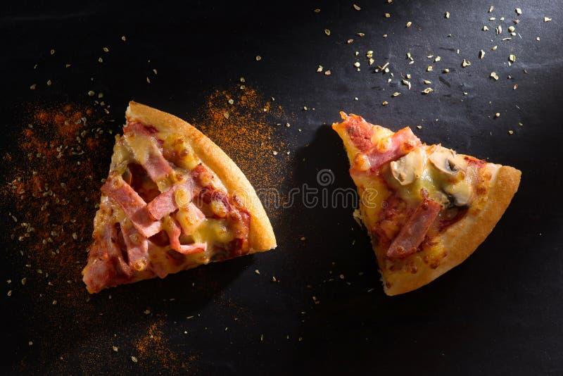 En skiva av pizza är på en stenplatta royaltyfri fotografi