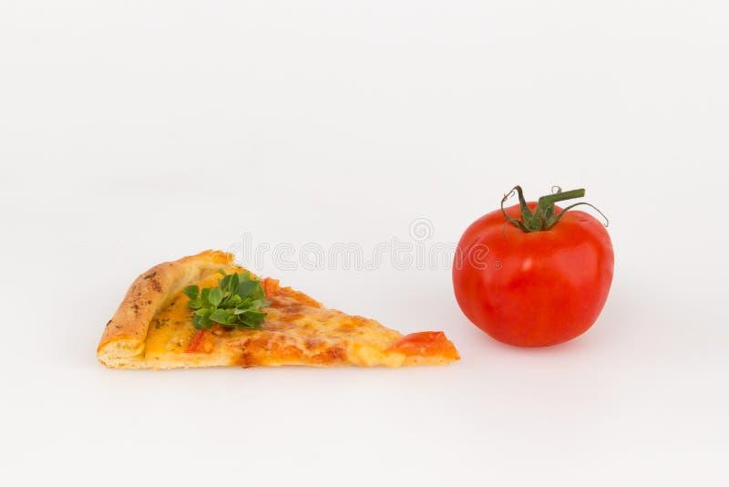 En skiva av pizza och den röda tomaten arkivbild