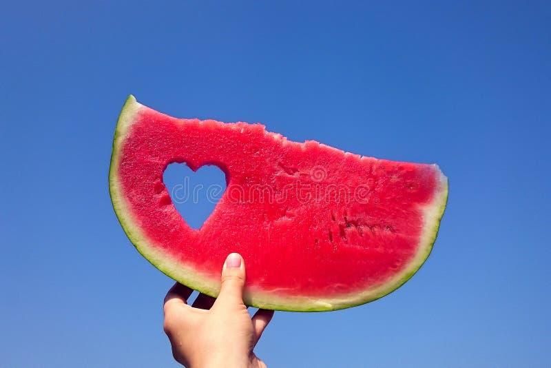 En skiva av vattenmelon och hjärta mot den ljusa sommarhimlen i handen för flicka` s arkivfoton