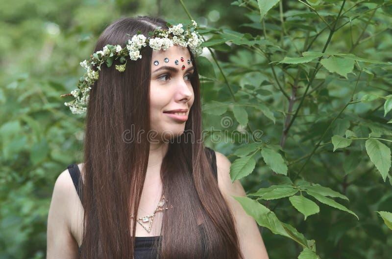 En skogbild av en härlig ung brunett av det europeiska utseendet med ögon för mörk brunt och stora kanter På flickan är huvudet royaltyfri fotografi