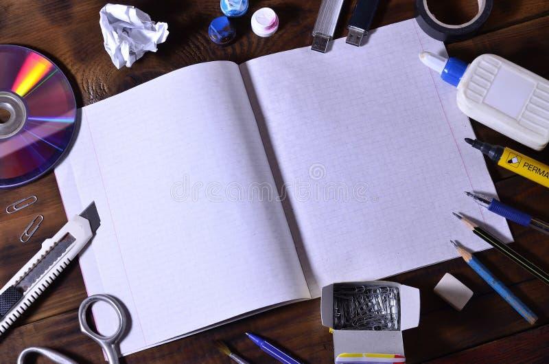 En skola- eller kontorsstilleben med en öppen skolaanteckningsbok eller checkhäfte och många kontorstillförsel Lögnen för skolati arkivbild