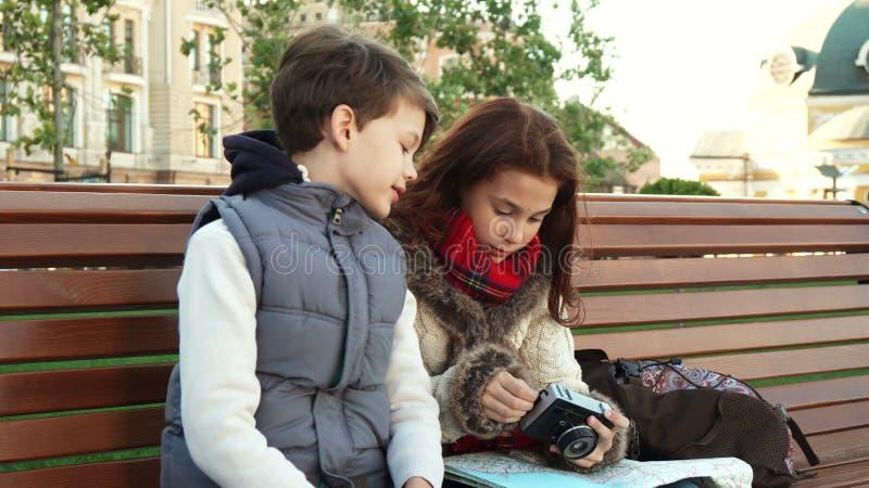 En skolaflicka och hennes vän sitter på en bänk och undersöker kameran royaltyfri foto