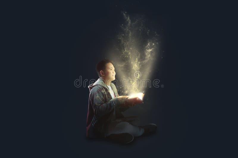 En skolapojke som bär ett omslagsinnehav och läsning en magisk bok med mystiskt ljust kommande ut Idéer från läsning Visa edu royaltyfri illustrationer