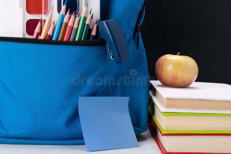 En skolaryggsäck med kulöra målarfärger i ett fack är på tabellen bredvid ett äpple arkivbilder