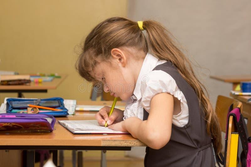En skolflicka i en huka sig ned kurs skriver i anteckningsbok arkivbilder
