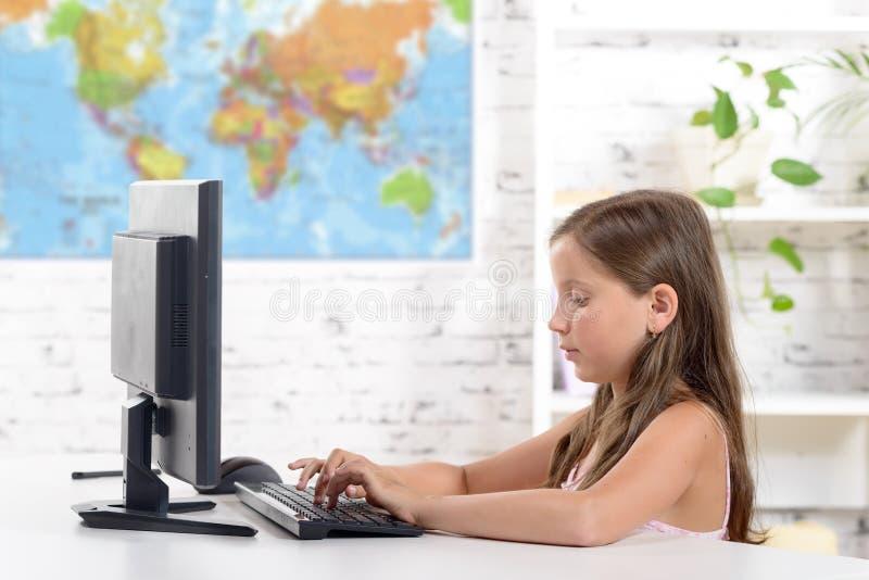 En skolflicka som arbetar på en dator fotografering för bildbyråer
