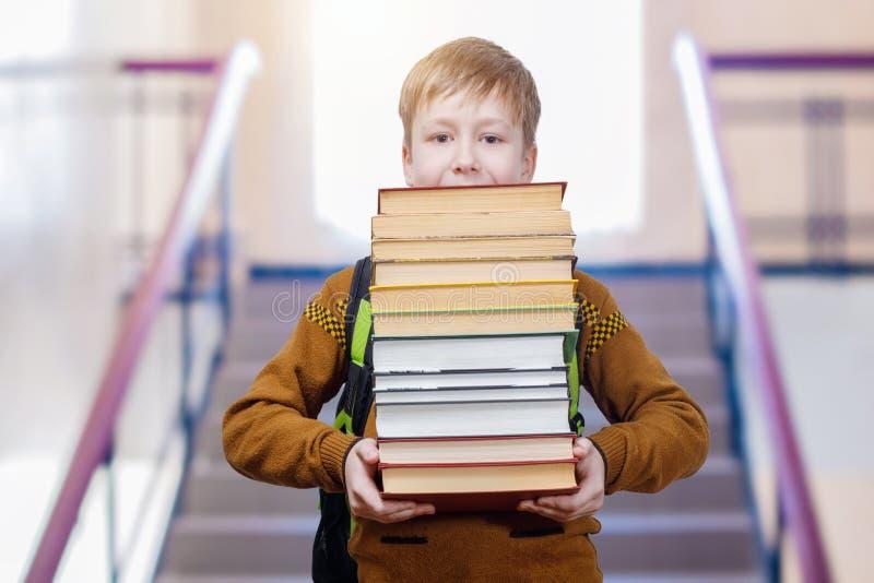 En skolpojke är den gående bottenvåningen med böcker i hans händer royaltyfri foto