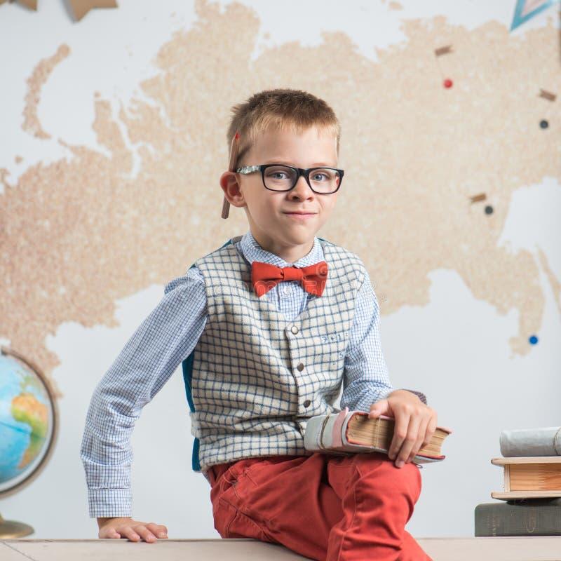 En skolpojke som bär exponeringsglas, sitter på ett skrivbord och rymmer en bok i hans händer arkivfoto