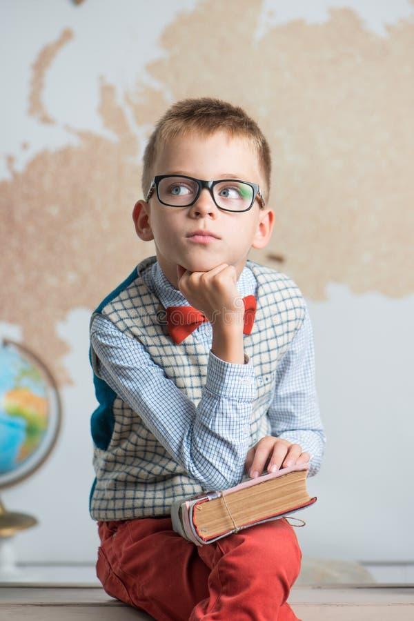 En skolpojke som bär exponeringsglas, sitter på ett skrivbord och rymmer en bok i hans händer royaltyfri bild