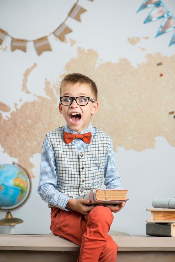 En skolpojke som bär exponeringsglas, sitter på ett skrivbord och rymmer en bok i hans händer royaltyfria bilder