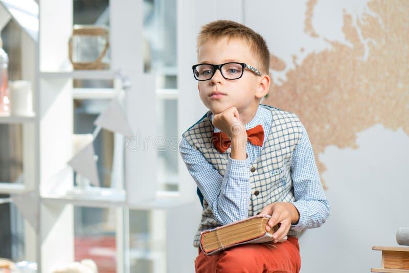 En skolpojke som bär exponeringsglas, sitter på ett skrivbord och rymmer en bok i hans händer arkivfoton