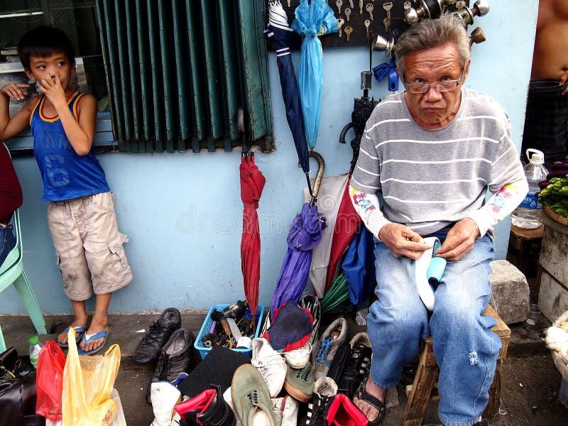 En skomakare reparerar en sko för en kund längs en gata i den Antipolo staden, Filippinerna arkivbild