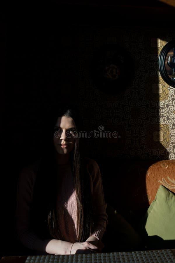 En skugga döljer halva framsidan av en flicka, när hon sitter i ett kafé i aftonen arkivbilder