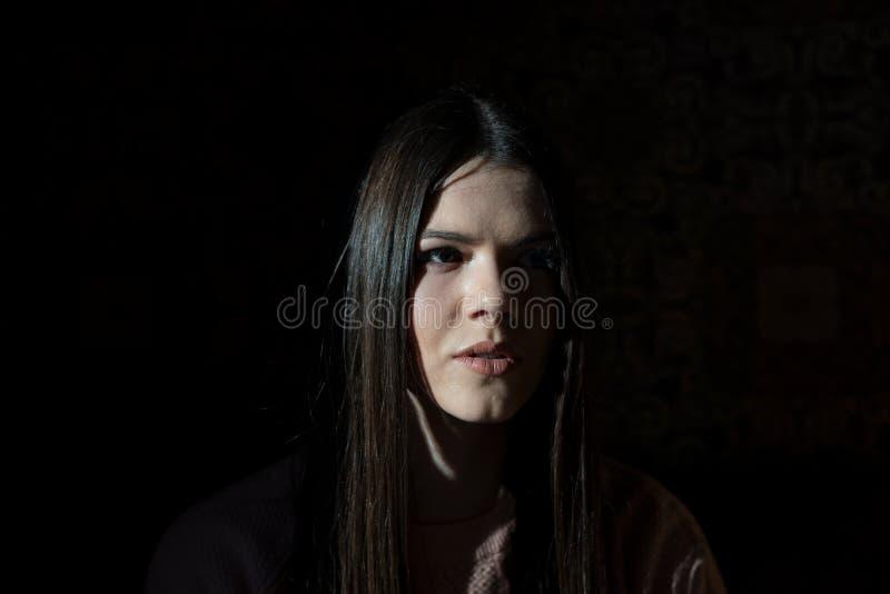 En skugga döljer halva framsidan av en flicka, när hon sitter i ett kafé i aftonen royaltyfria foton