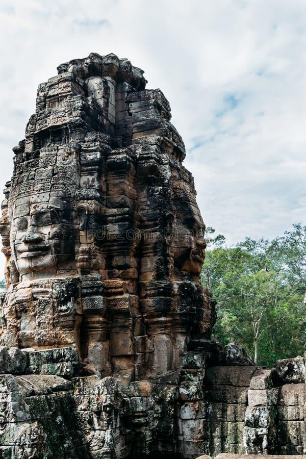 En skulptur som snidas från ett lantligt, vaggar i form av framsidor på fyra av dess delar på taken av fördärvar av den Bayon tem royaltyfri foto