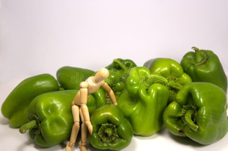 En skyltdocka som upp väljer pepparen för att ta dem till köket royaltyfri fotografi