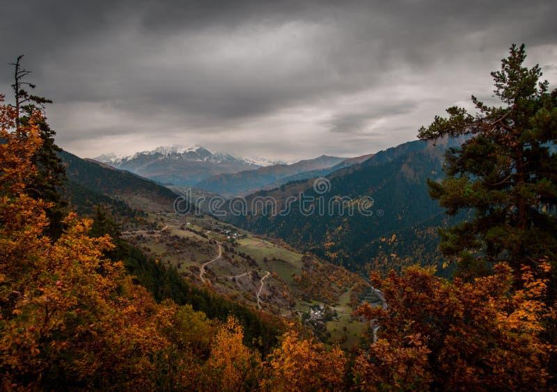 En slingrig väg passerar till och med byar i Georgia mot bakgrunden av berg arkivfoto