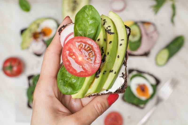 En smörgås med den nya tomaten och avokadot i kvinnlig hand close upp Sommarmellanmål och superfood arkivfoton