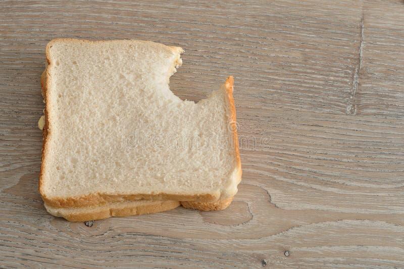 En smörgås med en tugga som tas ut ur den royaltyfri bild