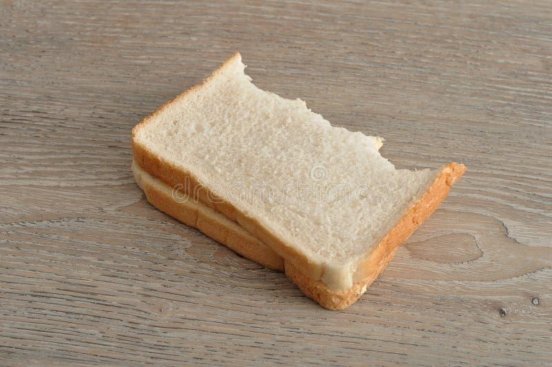 En smörgås med en tugga som tas ut ur den arkivbild