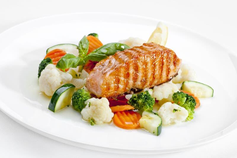 En smaklig mat. Grillade lax och grönsaker. Högkvalitativ bild royaltyfri fotografi