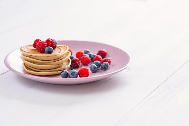 En smaklig och sund frukost av pannkakor med hallon och blåbär royaltyfri foto