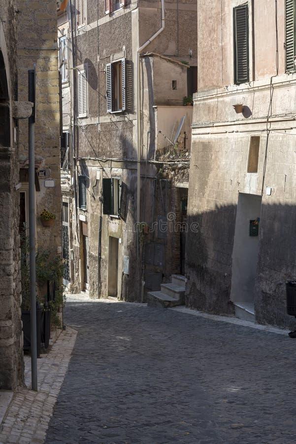 En smal gata i staden av Rome, vägen av kullersten och gamla hus arkivbild
