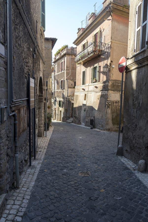 En smal gata i staden av Rome, vägen av kullersten och gamla hus royaltyfria bilder