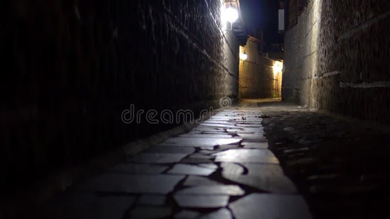 En smal mörk fasagata på natten arkivbild
