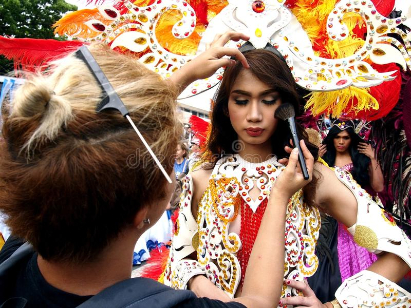 En sminkkonstnär applicerar smink till en ståtadeltagare i hennes färgrika dräkt under den Sumaka festivalen i den Antipolo stade royaltyfri bild