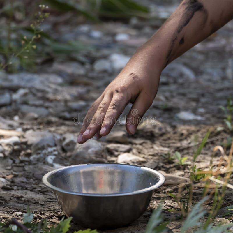 En smutsig hand når för en metallplatta som står på marken Begreppet slaveri, hunger, våld och barn royaltyfria foton
