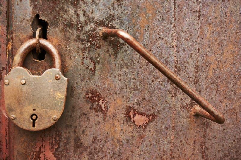 En smutsig rostig dörr för gammal metall med en hänglås abstrakt bakgrund arkivbilder