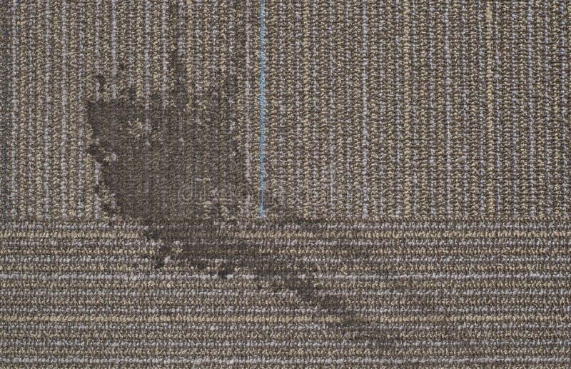 En smutsig vätskefläck på en vanlig matta arkivbilder
