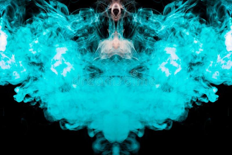 En snöig modell med hjälpen av den ljusa färgrika backlightingen i blå och utandas rök som fångas i ett foto som isoleras på en s arkivfoton